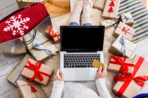 Woman shopping online surrounded by holiday gifts
