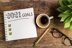 Notebook saying 2021 goals on a rustic table