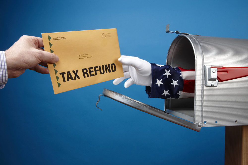 Arm of Uncle Sam delivering a tax refund out of a mailbox