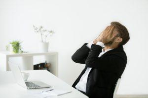 Man upset at his computer covering his face