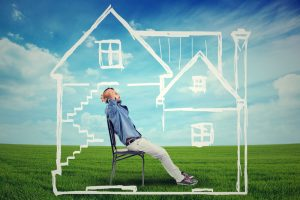 Man inside a chalk drawing of a house against blue sky and green grass